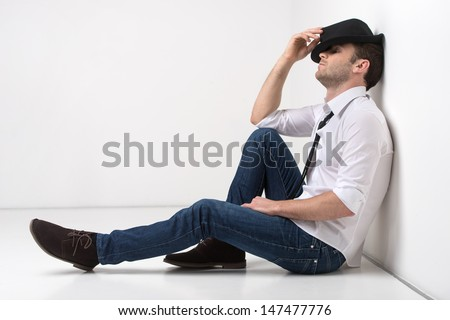 Waiting for inspiration. Young funky men in black hat leaning on the wall and looking away - stock photo