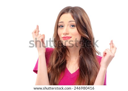 Waiting for special moment. Cheerful young caucasian woman looking at camera and keeping fingers crossed while standing isolated on white. Concept of wishing or praying about something - stock photo