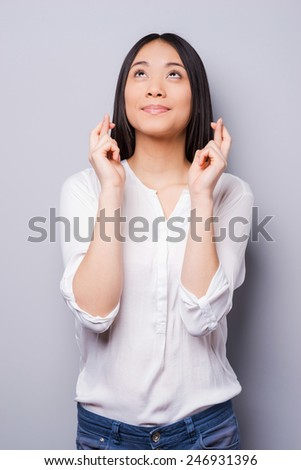Waiting for special moment. Cheerful young woman looking up and keeping fingers crossed while standing against grey background - stock photo