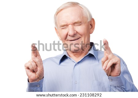 Waiting for special moment. Portrait of senior man in shirt keeping fingers crossed and eyes closed while standing against white background - stock photo