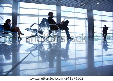 Waiting room with passengers in the airport - stock photo