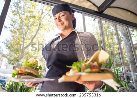 waitress bringing two piadinas at table. concept about service and food - stock photo