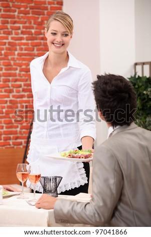 Waitress handing meal to customer - stock photo