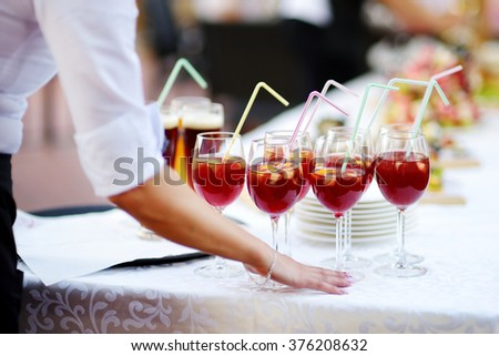 Waitress holding a dish of sangria and wine glasses at some festive event, party or wedding reception