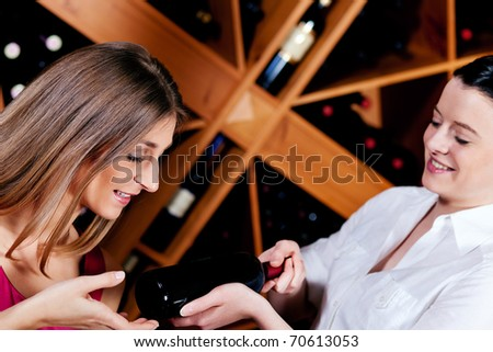 Waitress in a wine bar or restaurant offers a bottle of red wine to a young woman - stock photo