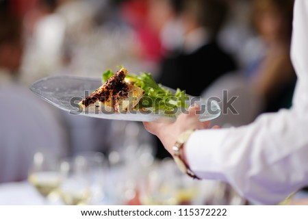Waitress is carrying a plate with meat dish - stock photo