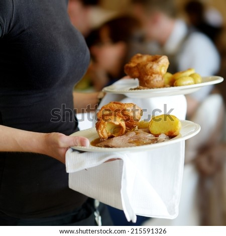 Waitress is carrying two plates with meat dish - stock photo