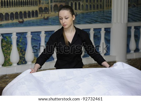 waitress lays tablecloth in restaurant - stock photo
