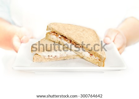 Waitress serving freshly made sandwich. She is holding a sandwich with a chicken and bacon filling in bright white, high key lighting. Shallow focus which is focused on the filling of the sandwich. - stock photo