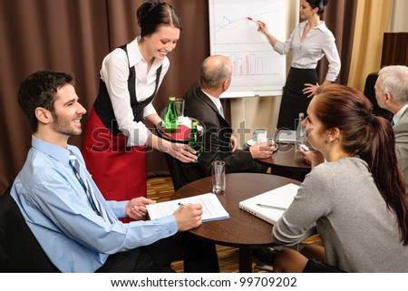 Waitress serving people at business meeting flip-chart presentation - stock photo
