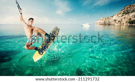 Wakeboarder making tricks on the sea in the sunny day. Wakeboarding on the beach. - stock photo