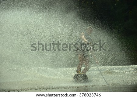 Wakeboarder silhouette moving fast in splashes of water at sunset - stock photo