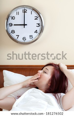 Waking up and yawning woman in bedroom - stock photo