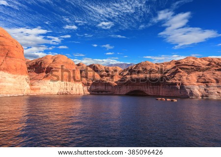 Walk by tourist motor ship on water on sunset. The lake is surrounded with amazing coast from orange sandstone. Picturesque artificial huge reservoir Powell on the river Colorado, USA - stock photo
