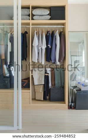 walk in closet with clothes hanging in wooden wardrobe at home - stock photo