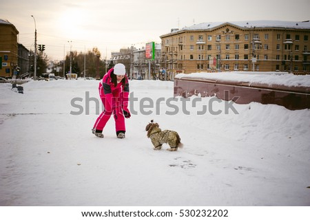 Walk in winter outdoors with dog breed Shih Tzu. A woman in bright red warm ski clothing walking in snow with your pet, little shih tzu dressed in overalls. care for animals loves playing with the dog