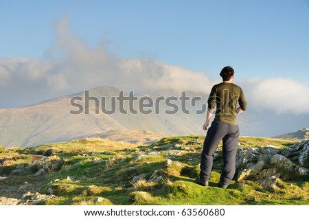 Walker admiring the view towards cloudy Fairfield, mountain in the English Lake District - stock photo
