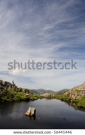 Walker and the tarn on the summit of Haystacks, English Lake District - stock photo