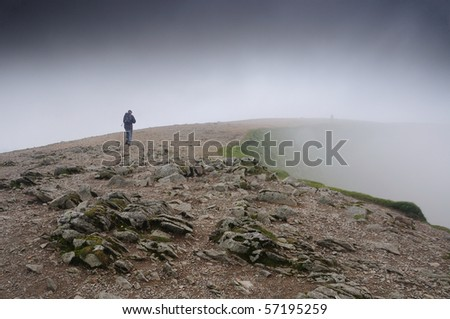 Walker in the mist on the summit of Helvellyn, English Lake District - stock photo