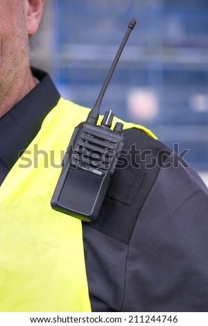 walkie-talkie on sholder of man i yellow vest - stock photo