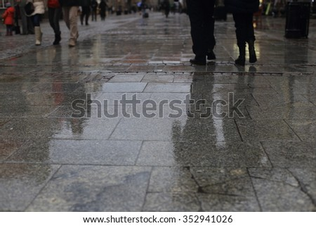 Walking along wet  pavement street. Rain in the city. - stock photo