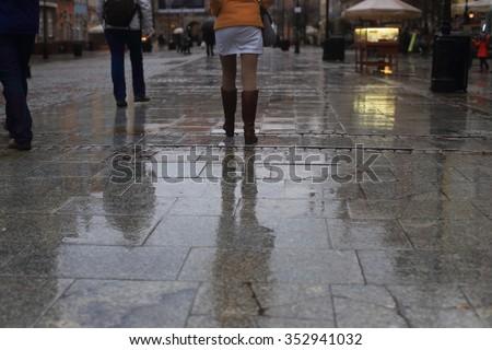 Walking along wet  pavement street. Rain in the city. - stock photo