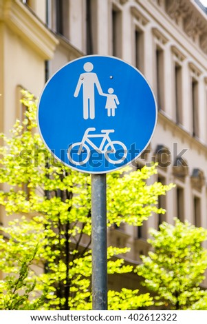 Walking and cycling way sign board - urban environment with trees and building facade - stock photo