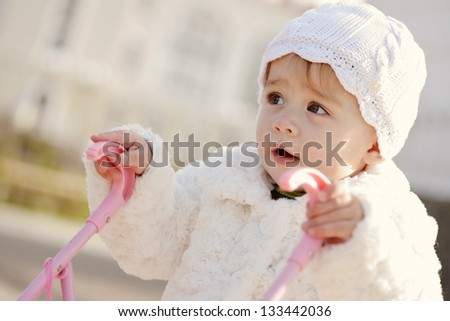 walking baby girl with toy stroller - stock photo