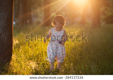 Walking baby in sunset lights - stock photo