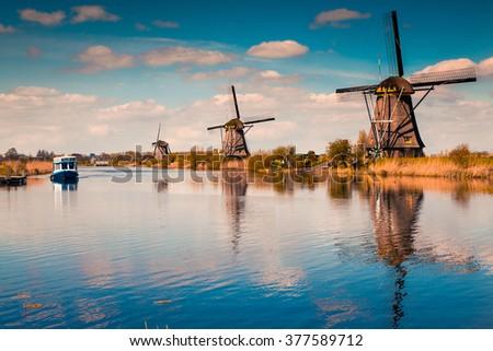 Walking boat on the famoust Kinderdijk canal with windmills. Old Dutch village Kinderdijk, UNESCO world heritage site. Netherlands, Europe. - stock photo