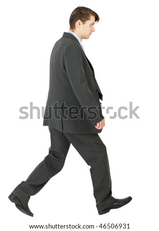 Walking businessman in a dark suit isolated on white background - stock photo