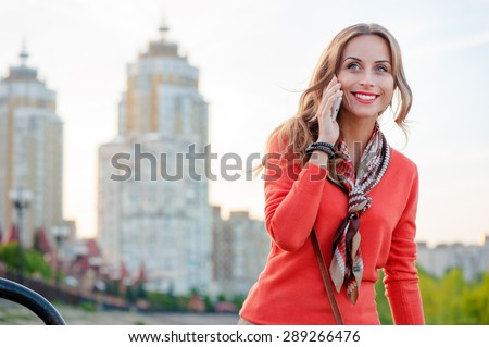 Walking by city. Attractive young woman talking on mobile phone outdoors. - stock photo