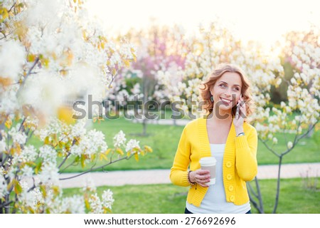 Walking by spring park. Attractive young woman talking by phone and holding cup of coffee outdoors. - stock photo