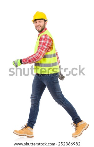 Walking construction worker in yellow helmet and lime reflective waistcoat. Full length studio shot isolated on white.  - stock photo