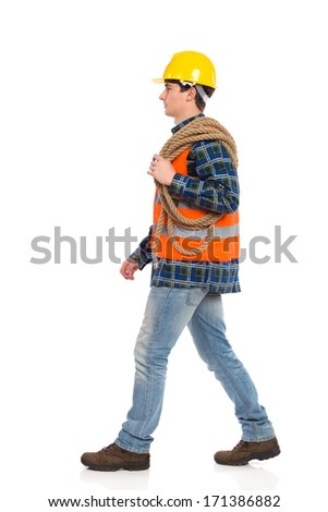 Walking construction worker in yellow helmet and orange waistcoat with rope on his shoulder.  Full length studio shot isolated on white. - stock photo
