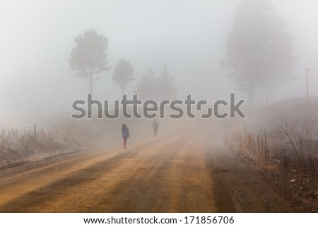 Walking Dirt Road Unidentified Young teenagers unidentified walking on farm mountain rural countryside dirt road in winter mist. - stock photo