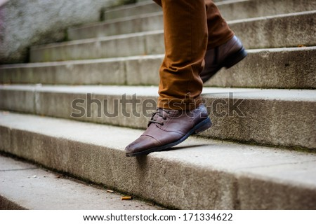 Walking downstairs: close-up view of man's leather shoes - stock photo