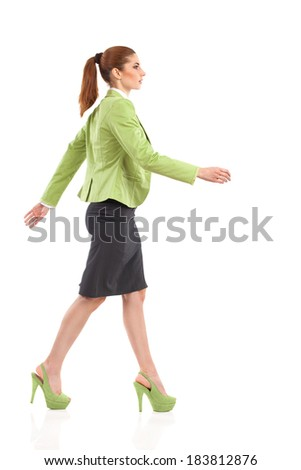 Walking elegance woman in green suit, mini skirt and high heels. Full length studio shot isolated on white. Side view. - stock photo
