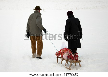 walking grandparents with child on a slide - stock photo