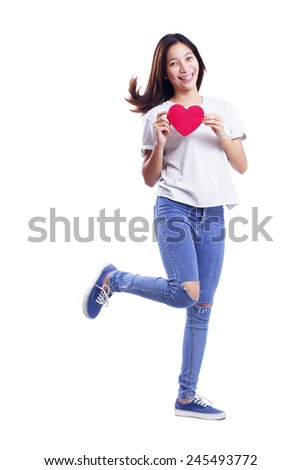 Walking happy young lady in casual outfit holding a heart shaped red card. Isolated in white background. - stock photo