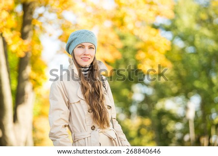Walking in autumn park, young woman over natural autumn background
