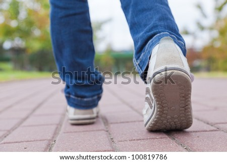 Walking in sport shoes on pavement in spring day - stock photo