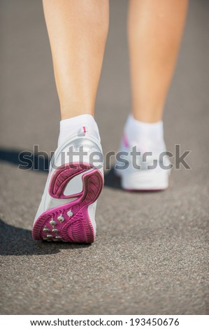 Walking in sports shoes.  Close-up image of woman in sports shoes walking  - stock photo