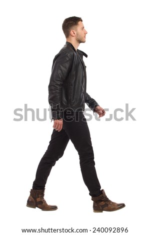 Walking man in black leather jacket and black jeans. Full length studio shot isolated on white. - stock photo