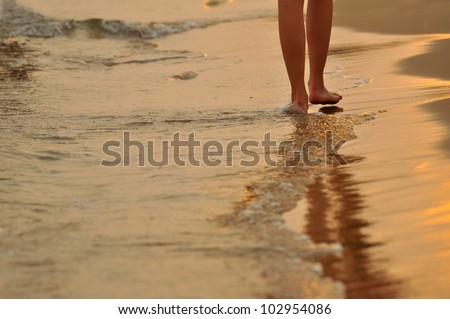 Walking on the beach in sunset time - stock photo