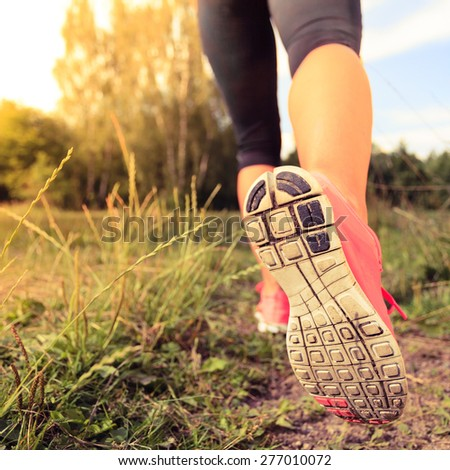 Walking or running exercise, legs on footpath in forest, motivation inspiration concept outdoors, achievement fitness adventure and exercising in spring or summer nature - stock photo
