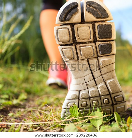 Walking or running exercise shoes close-up, legs on green grass footpath in forest, achievement fitness adventure and exercising in spring or summer nature - stock photo