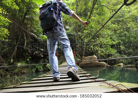 walking outdoor hanging bridge over the little winding brook in forest - stock photo
