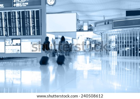 Walking passengers with baggage in airport terminal. Blur motion - stock photo