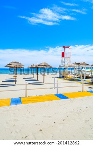 Walking path along sandy Villasimius beach with lifeguard tower and sun umbrellas, Sardinia island, Italy - stock photo